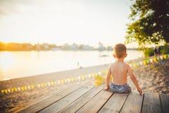 Το θέμα είναι διακοπές παραλιών παιδιών και καλοκαιριού Ένα μικρό καυκάσιο αγόρι κάθεται λοξά σε μια ξύλινη αποβάθρα και θαυμάζει Στοκ φωτογραφία με δικαίωμα ελεύθερης χρήσης