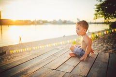 Το θέμα είναι διακοπές παραλιών παιδιών και καλοκαιριού Ένα μικρό καυκάσιο αγόρι κάθεται λοξά σε μια ξύλινη αποβάθρα και θαυμάζει Στοκ Φωτογραφία