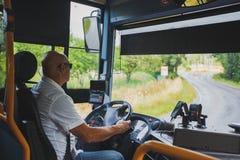 Το θέμα είναι το επάγγελμα της μεταφοράς οδηγών και επιβατών Ένα άτομο στον οδηγό γυαλιών ηλίου Α οδηγεί ένα περιφερειακό λεωφορε στοκ φωτογραφίες
