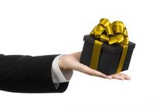 Το θέμα των εορτασμών και των δώρων: ένα άτομο σε ένα μαύρο κοστούμι που κρατά ένα αποκλειστικό δώρο συσκευασμένο σε ένα μαύρο κο Στοκ Εικόνα
