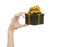 Το θέμα των εορτασμών και των δώρων: χέρι που κρατά ένα δώρο τυλιγμένο σε ένα μαύρο κουτί με τη χρυσά κορδέλλα και το τόξο, το ομ Στοκ εικόνα με δικαίωμα ελεύθερης χρήσης