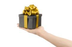 Το θέμα των εορτασμών και των δώρων: χέρι που κρατά ένα δώρο τυλιγμένο σε ένα μαύρο κουτί με τη χρυσά κορδέλλα και το τόξο, το ομ Στοκ φωτογραφία με δικαίωμα ελεύθερης χρήσης