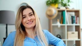Το θαυμάσιο χαμογελώντας κορίτσι με ένα καλό βλέμμα και φυσικός αποτελεί την εξέταση τη κάμερα στο άνετο δωμάτιο Πορτρέτο προσώπο απόθεμα βίντεο