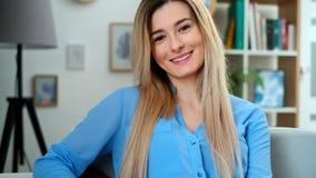 Το θαυμάσιο χαμογελώντας κορίτσι με ένα καλό βλέμμα και φυσικός αποτελεί την εξέταση τη κάμερα στο άνετο δωμάτιο Κλείστε επάνω το απόθεμα βίντεο