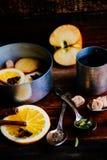 Το θερμαμένο ζεστό ποτό κρασιού με τα εσπεριδοειδή, το μήλο και τα καρυκεύματα casserole και το FIR αργιλίου διακλαδίζονται στο σ Στοκ Εικόνες