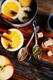 Το θερμαμένο ζεστό ποτό κρασιού με τα εσπεριδοειδή, το μήλο και τα καρυκεύματα casserole και το FIR αργιλίου διακλαδίζονται στο σ Στοκ Εικόνα