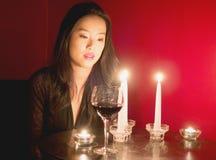 Το θερμό φως κεριών φωτίζει το γυναικείο πρόσωπο δεδομένου ότι συλλογίζεται το ποτήρι του κόκκινου κρασιού Στοκ Φωτογραφία