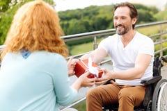 Το θετικό το ανώτερο άτομο που δίνει ένα παρόν στη σύζυγό του στοκ εικόνες