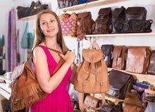 Το θετικό ενήλικο θηλυκό στη λεωφόρο αγορών επιλέγει το σακίδιο πλάτης στοκ φωτογραφία με δικαίωμα ελεύθερης χρήσης