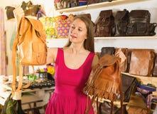 Το θετικό ενήλικο θηλυκό στη λεωφόρο αγορών επιλέγει το σακίδιο πλάτης στοκ εικόνες