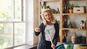 Το θετικό κορίτσι χορεύει με την επίπεδη σφουγγαρίστρα και τραγουδώντας κάνοντας τα οικιακά στο σπίτι, η νέα γυναίκα έχει τη διασ απόθεμα βίντεο