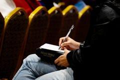 Το θηλυκό ακούει το κήρυγμα και γράψιμο κάτι σε χαρτί στοκ εικόνα