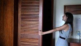 Το θηλυκό ανοίγει την πόρτα ντουλαπιών και επιλέγει τι να φορέσει 4K απόθεμα βίντεο