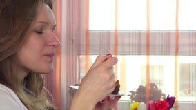 Το θηλυκό απολαμβάνει το γλυκό κέικ στο φωτεινά παράθυρο και το υπόβαθρο λουλουδιών απόθεμα βίντεο