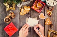 Το θηλυκό γράψιμο χεριών τοπ άποψης επιθυμεί στη ευχετήρια κάρτα για αγαπημένη για τα Χριστούγεννα Ξύλινος πίνακας με το ντεκόρ,  Στοκ εικόνα με δικαίωμα ελεύθερης χρήσης