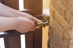 Το θηλυκό γυρίζει το κλειδί στην κλειδαριά στην εξωτερική πόρτα ανοικτή, PU Στοκ Φωτογραφίες