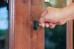 Το θηλυκό γυρίζει το κλειδί στην κλειδαριά στην εξωτερική πόρτα ανοικτή, PU Στοκ εικόνα με δικαίωμα ελεύθερης χρήσης