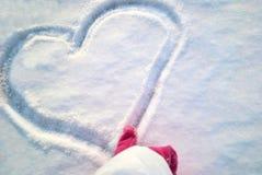 Το θηλυκό δάχτυλο στα κόκκινα γάντια σύρει μια καρδιά στο χιόνι Στοκ Φωτογραφία