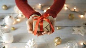 Το θηλυκό δίνει ένα κιβώτιο δώρων με τη διακόσμηση και τα φω'τα Chritmas φιλμ μικρού μήκους