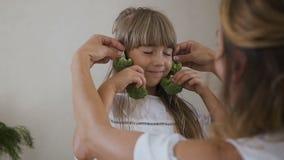 Το θηλυκό δύο ενός μικρού κοριτσιού και το mom της παίζουν και κάνουν τα σκουλαρίκια χρησιμοποιώντας το φρέσκο μπρόκολο Όμορφο κο απόθεμα βίντεο