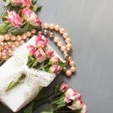 Το θηλυκό επίπεδο βάζει τα λουλούδια, το δώρο και το περιδέραιο τριαντάφυλλων σκηνής στο γκρίζο ουδέτερο υπόβαθρο Τοπ όψη Στοκ φωτογραφία με δικαίωμα ελεύθερης χρήσης
