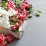 Το θηλυκό επίπεδο βάζει τα φρέσκα λουλούδια και το δώρο τριαντάφυλλων σκηνής στο γκρίζο ουδέτερο υπόβαθρο Τοπ όψη διάστημα αντιγρ Στοκ εικόνα με δικαίωμα ελεύθερης χρήσης