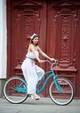 Το θηλυκό κάθεται στο ποδήλατο ενάντια στην παλαιά κόκκινη πόρτα υποβάθρου στοκ φωτογραφίες με δικαίωμα ελεύθερης χρήσης
