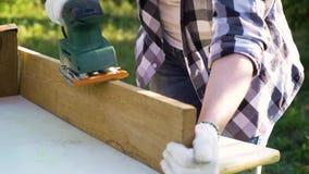 Το θηλυκό κινηματογραφήσεων σε πρώτο πλάνο παραδίδει τα λειτουργώντας γάντια γυαλίζει την ξύλινη σανίδα με ηλεκτρικό sander φιλμ μικρού μήκους