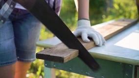 Το θηλυκό κινηματογραφήσεων σε πρώτο πλάνο παραδίδει τα προστατευτικά γάντια που πριονίζουν την ξύλινη σανίδα έξω φιλμ μικρού μήκους