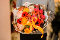 Το θηλυκό κρατά μια ανθοδέσμη με τα pion-διαμορφωμένα τριαντάφυλλα, τις παπαρούνες, τα ρόδινα και πορτοκαλιά τριαντάφυλλα Στοκ Εικόνα