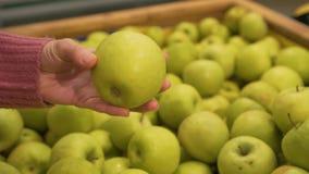 Το θηλυκό μαζεύει με το χέρι τα μήλα στην υπεραγορά απόθεμα βίντεο