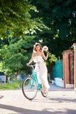 Το θηλυκό οδηγά το εκλεκτής ποιότητας ποδήλατο με τα peonies στο υπόβαθρο των πρασίνων στοκ φωτογραφία με δικαίωμα ελεύθερης χρήσης