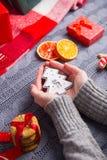 Το θηλυκό παραδίδει την γκρίζα πλεκτή εκμετάλλευση πουλόβερ στο ντεκόρ Χριστουγέννων Στοκ Φωτογραφία