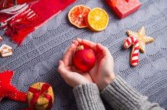 Το θηλυκό παραδίδει την γκρίζα πλεκτή σφαίρα Χριστουγέννων εκμετάλλευσης πουλόβερ στο δ Στοκ Φωτογραφίες