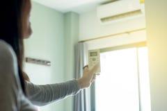 Το θηλυκό που χρησιμοποιεί τον τηλεχειρισμό στην υπαίθρια βελτίωση στην κρεβατοκάμαρα, κλείνει επάνω στοκ φωτογραφία με δικαίωμα ελεύθερης χρήσης