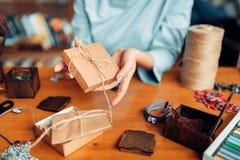 Το θηλυκό πρόσωπο δένει ένα τόξο σε ένα κιβώτιο δώρων, ραπτική Στοκ εικόνα με δικαίωμα ελεύθερης χρήσης