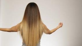 Το θηλυκό πρότυπο παρουσιάζει στη μακριά υγιή ξανθή τρίχα της πίσω άποψη σε αργή κίνηση απόθεμα βίντεο