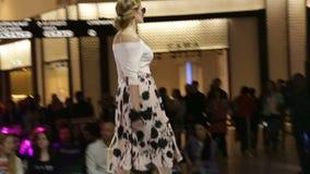 Το θηλυκό πρότυπο πλάγιας όψης παρουσιάζει την μπλούζα και τσάντα φουστών απόθεμα βίντεο