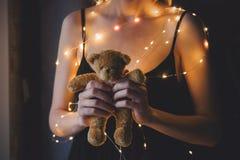 Το θηλυκό στο μαύρο φόρεμα και τα φω'τα που κρατούν teddy αντέχουν το παιχνίδι Στοκ εικόνα με δικαίωμα ελεύθερης χρήσης