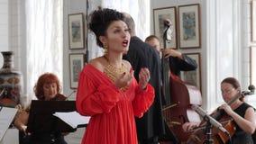 Το θηλυκό τραγουδιστών στο κόσμημα και το κόκκινο φόρεμα τραγουδά στην ορχήστρα και τον αγωγό υποβάθρου απόθεμα βίντεο