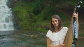Το θηλυκό χέρι αγγίζει ήπια τις σειρές του bandura στον καταρράκτη απόθεμα βίντεο