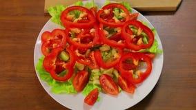 Το θηλυκό χέρι βάζει έξω τα δαχτυλίδια του κόκκινου πιπεριού σε ένα πιάτο με το μαρούλι και τις ντομάτες απόθεμα βίντεο