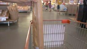 Το θηλυκό χέρι βάζει μια φραντζόλα του ψωμιού στο κάρρο στην υπεραγορά, κινηματογράφηση σε πρώτο πλάνο απόθεμα βίντεο