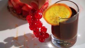 Το θηλυκό χέρι βάζει τη σταφίδα σε ένα πιάτο σκηνή Πιάτο με τα εύγευστα μούρα και το ποτό απόθεμα βίντεο