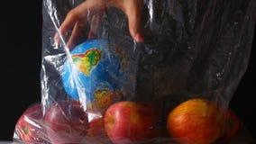 Το θηλυκό χέρι βάζει τη σφαίρα σε μια τσάντα με τα μήλα εικόνες οικολογίας έννοιας πολύ περισσότεροι το χαρτοφυλάκιό μου απόθεμα βίντεο