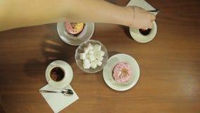 Το θηλυκό χέρι βάζει τους κύβους ζάχαρης στα φλυτζάνια του καυτού καφέ απόθεμα βίντεο