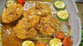 Το θηλυκό χέρι γυρίζει τα κομμάτια των λαχανικών με τις λαβίδες και του κοτόπουλου σε ένα τηγάνι σχαρών απόθεμα βίντεο