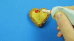 Το θηλυκό χέρι επισύρει την προσοχή απαγορευμένος emoticons διαμορφωμένα στα καρδιά μπισκότα σε ένα μπλε υπόβαθρο απόθεμα βίντεο