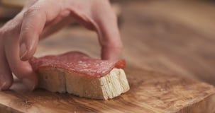 Το θηλυκό χέρι κάνει τη φέτα baguette σάντουιτς με το τυρί και το σαλάμι κρέμας Στοκ φωτογραφία με δικαίωμα ελεύθερης χρήσης