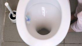 Το θηλυκό χέρι καθαρίζει το άσπρο κύπελλο τουαλετών με μια βούρτσα φιλμ μικρού μήκους